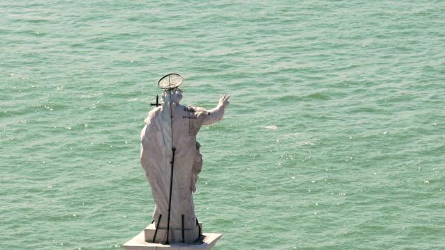 vidéos et rushes de moyenne de statue du saint homme dans rivière journée ensoleillée, les marins de la bénédiction avec le geste - baptême
