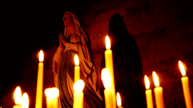Holy statue of Mary with candles video