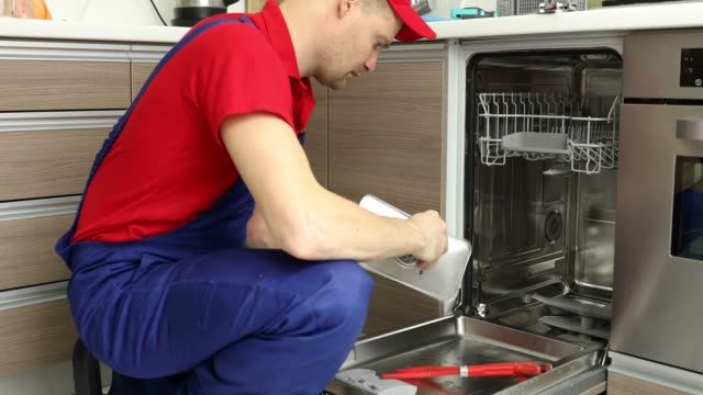 home appliance maintenance service - repairman working with dishwasher in domestic kitchen home appliance maintenance service - repairman working with dishwasher in domestic kitchen appliance stock videos & royalty-free footage