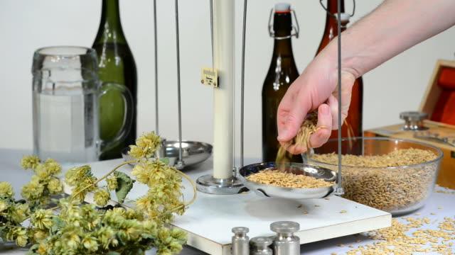 Home brewing of beer. Man weighs barley.