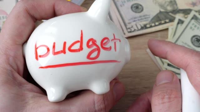 haushalt und finanzen wohnkonzept. man zieht ein wort budget auf ein sparschwein. - teurer lebensstil stock-videos und b-roll-filmmaterial