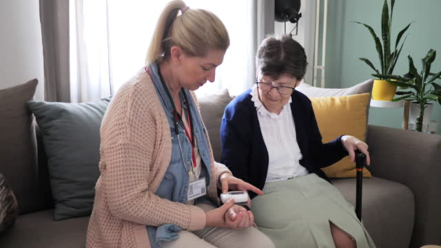 Home care and assisted living, senior woman and mature nurse at home Mature female nurse visiting patient at home and having medical examination such as blood pressure, physical therapy and body temperature mental wellbeing stock videos & royalty-free footage
