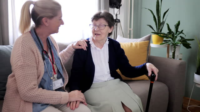 Home care, senior woman with walking cane and nurse administering medication