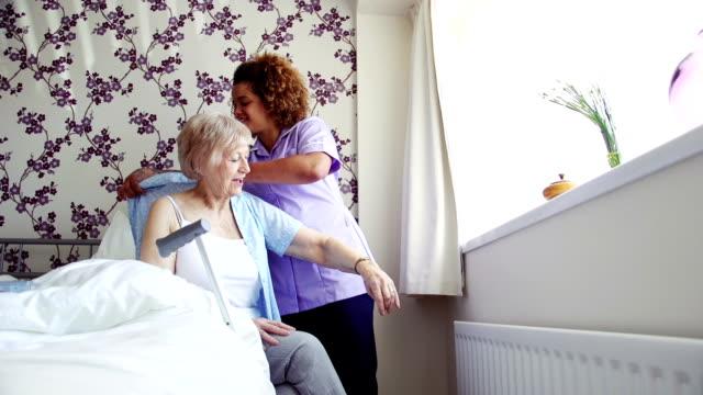 home caregiver dressing senior - care home stock videos & royalty-free footage