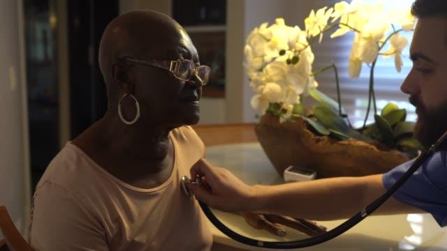 Home caregiver examining senior woman