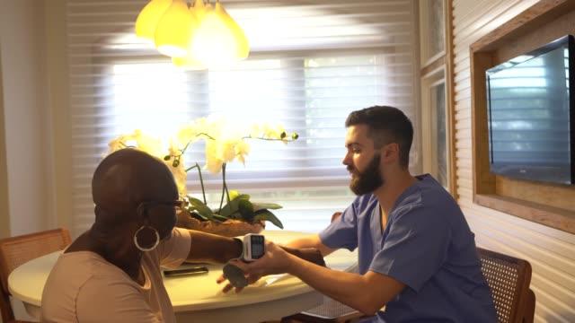 hem vårdgivare undersöker senior kvinna - vårdklinik bildbanksvideor och videomaterial från bakom kulisserna
