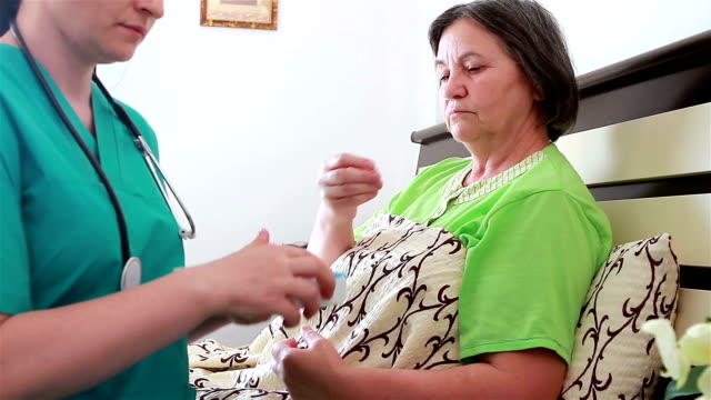 Home caregiver giving medicine to senior woman video