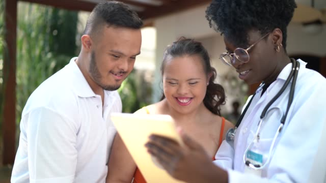 Home caregiver showing exam results to a special needs couple
