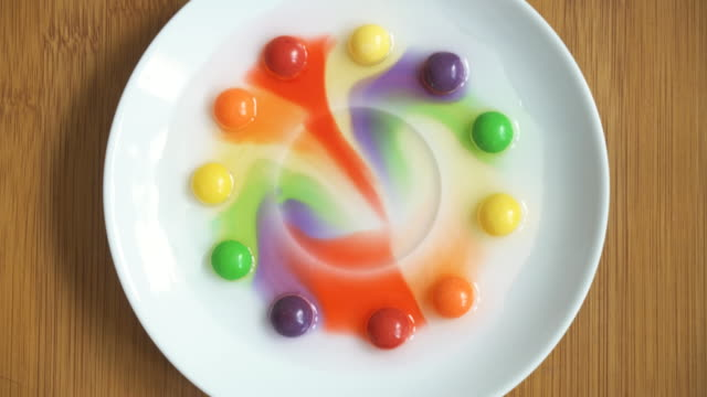 home chemistry. dye from sweets dissolves in water. - disolves stock videos and b-roll footage