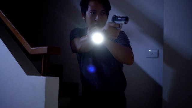 4 k ホーム防衛構想、アジア男持株ピストルと夜懐中電灯。 - デイフェンス点の映像素材/bロール