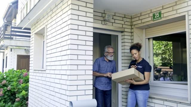 hemleverans av en låda till kunden - posttjänsteman bildbanksvideor och videomaterial från bakom kulisserna