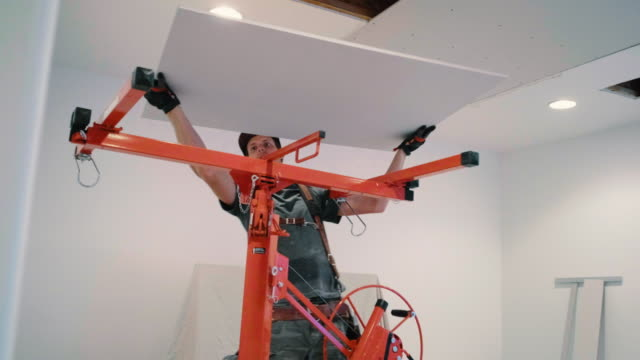 Home Drywall Repair A worker replaces a section of ceiling drywall while repairing a home interior. renovation stock videos & royalty-free footage