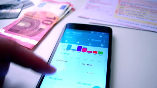 eigenheim-finanzierung-app auf dem smartphone, fallende graphen der bericht der ausgaben auf dem bildschirm. - haushaltskosten stock-videos und b-roll-filmmaterial