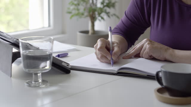 Home finance Senior woman sitting at a desk and  calculating family budget. financial planning stock videos & royalty-free footage