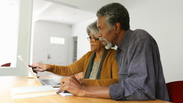 home finances on computer by african american senior couple - coppia anziana video stock e b–roll