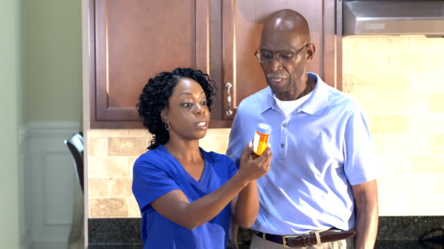 Home health aid helping senior man with medication