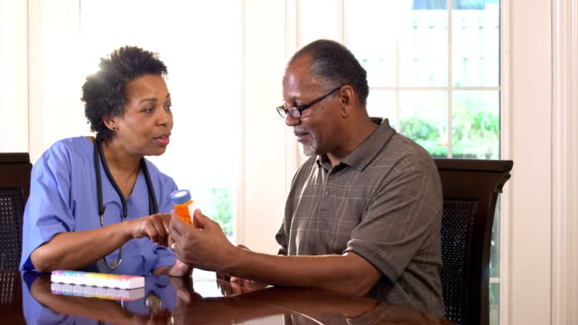 Home health care nurse helping senior man with medicine