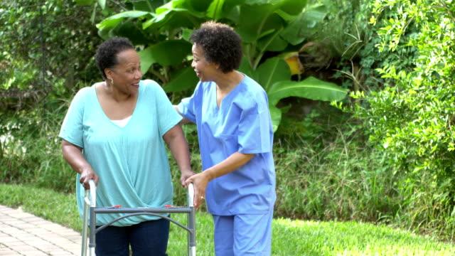 Home health care nurse helping senior woman with walker
