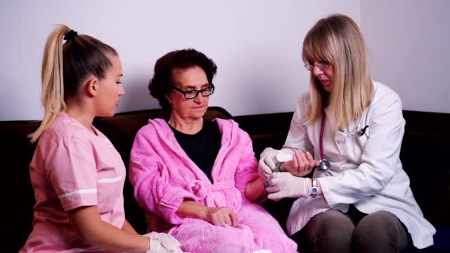 vídeos y material grabado en eventos de stock de médico a domicilio cuidado de la salud comprueba la presión arterial de la mujer mayor - geriatría