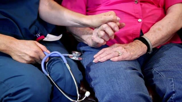 vídeos y material grabado en eventos de stock de enfermera profesional de la salud casa evalúa a pacientes adultos mayores en hogar de ancianos. - servicios sociales