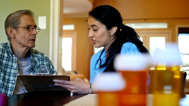 Home healthcare nurse reviews plan of care with senior patient