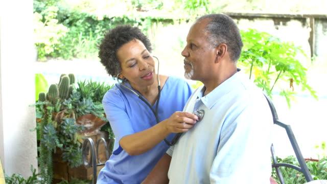 operatore sanitario a domicilio che esamina l'uomo anziano - torace umano video stock e b–roll