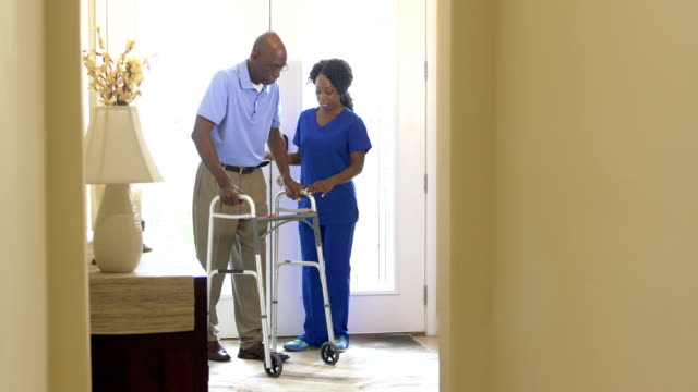 Home healthcare worker helping senior man with walker A home healthcare worker helping a senior African-American man with a walker. They are at the front door inside his home. orthopedic equipment stock videos & royalty-free footage