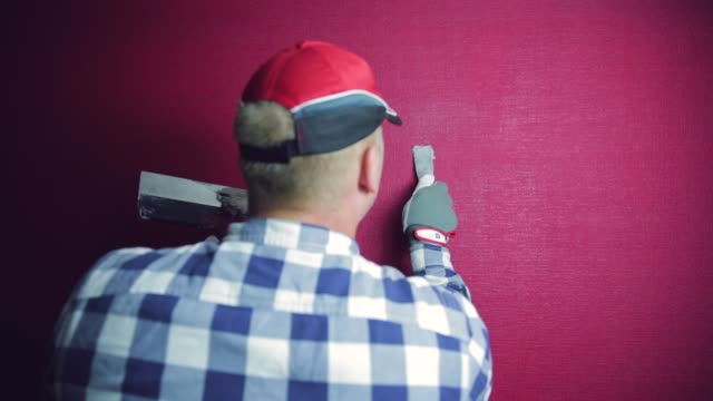 Home improvement. Handy man fills a hole with filler. House renovation