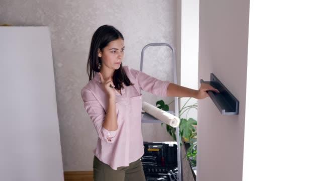 heminredning, leende flicka gör renovering och hänger hylla på väggen på rummet - hänga bildbanksvideor och videomaterial från bakom kulisserna
