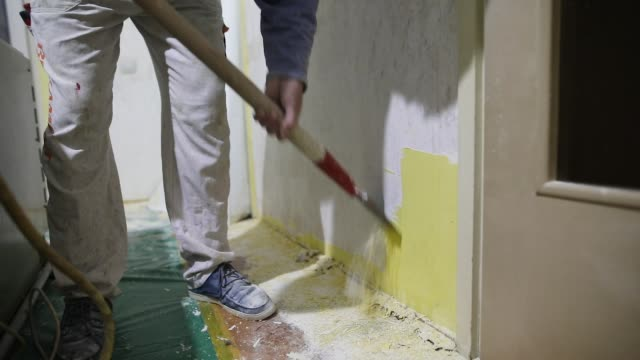 Home improvement, worker removes old, yellow paint from concrete wall with scraper