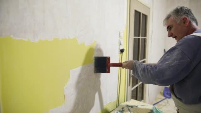 home improvement, worker removes old, yellow paint from concrete wall with scraper - szpatułka przybór do gotowania filmów i materiałów b-roll