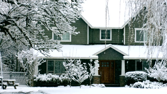 Home in winter with snow falling, slow motion video