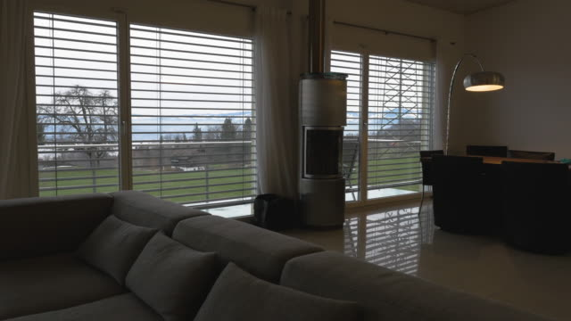 home interior with automatic blinds leading to a vista of swiss mountain scenery - penombra video stock e b–roll