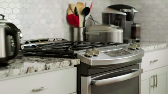 Home Kitchen Appliances A home kitchen counter with appliances stove, coffee machine, rich cooker, utensils. stainless steel stock videos & royalty-free footage