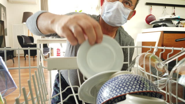Home quarantine for coronavirus COVID-19 epidemic. Middle age man wearing a protective face mask is to empty the dishwasher at home