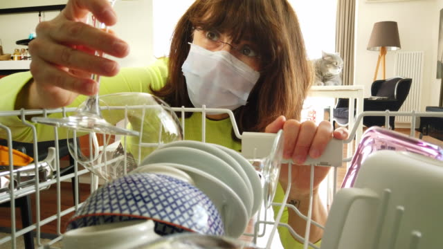 Home quarantine for coronavirus COVID-19 epidemic. Middle age woman wearing a protective face mask is to empty the dishwasher at home