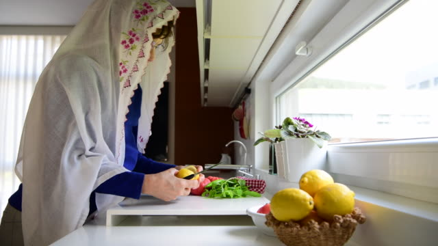 Home quarantine for coronavirus COVID-19 epidemic. Middle aged muslim woman cutting pita bread at home with headscarf