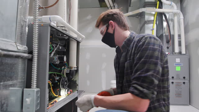 Home Repairman Wearing a Face Mask for Protection A repairman working inside a home, wearing a face mask for protection. furnace stock videos & royalty-free footage