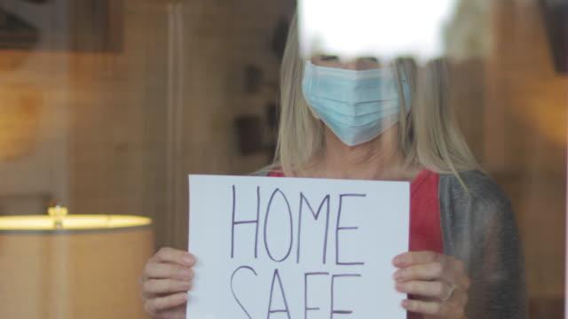 vídeos y material grabado en eventos de stock de hogar seguro durante la crisis de la enfermedad aerotransportada madura mujer refugio en casa durante la cuarentena de señales de mano 4k serie de videos - stay home