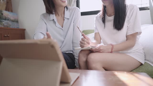 Home school teacher and Asian student during private tuition program, giving out ideas thoughts discussion, advisor  sitting on living room couch, digital learning media on tablet, study at home