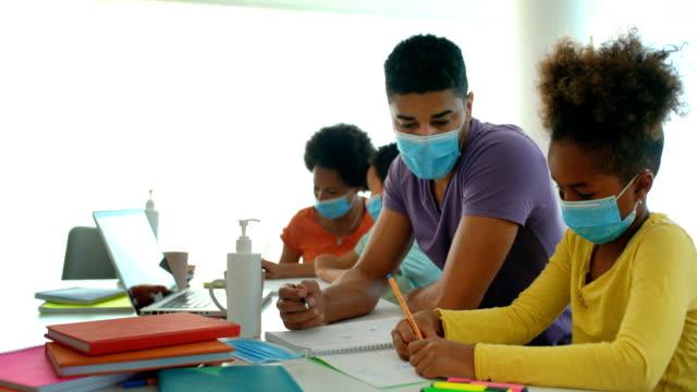vidéos et rushes de enseignement à domicile pendant la quarantaine de coronavirus. - enfant masque