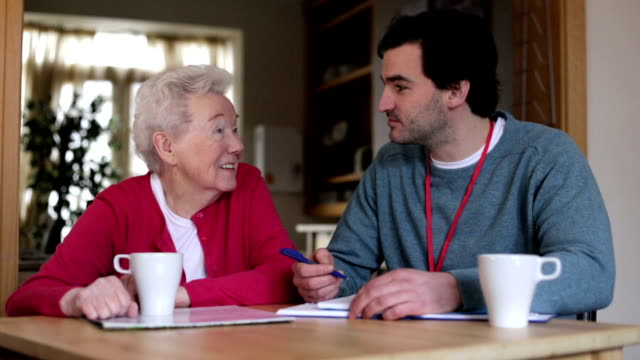 Home Visit A happy senior woman smiles as she sits with a male community worker talking over notes that are on his notepad. They both have a cup in front of them with a hot drink. sociology stock videos & royalty-free footage