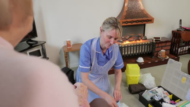 Home Visits For the Elderly A nurse sits on her knees after assisting an elderly lady. The senior woman is happy sitting in her armchair. They are both face to face chatting and enjoying a hot drink. nhs stock videos & royalty-free footage