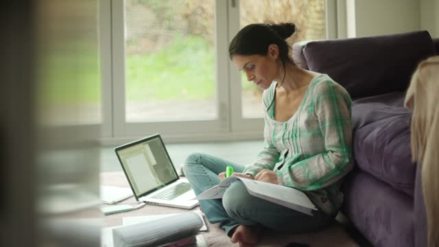 Home worker 4K stock video clip of good looking Hispanic woman working from home. She's seated on the floor of her living room with a laptop & a variety of stationery, behind her are large glass doors opening out to her back yard. university student stock videos & royalty-free footage