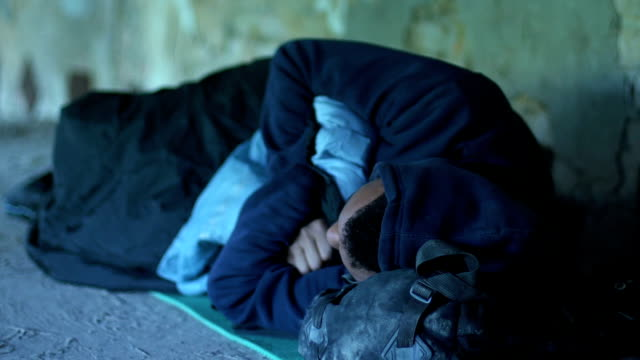 Homeless afro-american boy sleeping in underground pass, misery and poverty