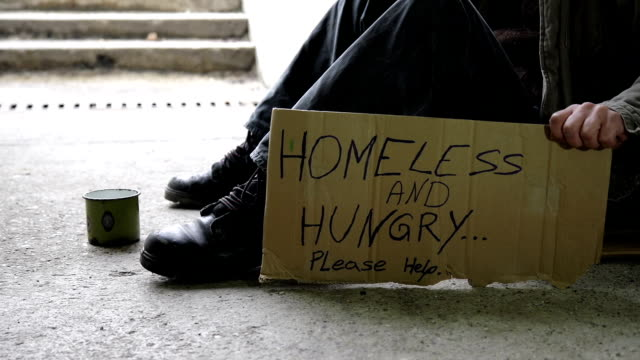 HD DOLLY: Homeless And Hungry HD1080p: DOLLY shot of a homeless person holding a cardboard sign with a message