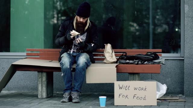 Hombre americano sin hogar y sin trabajo con cartón muestra comer sandwich en Banco en la calle de la ciudad debido a la crisis de los inmigrantes en Estados Unidos - vídeo