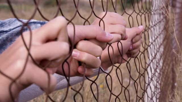homeless child. children's hands on a metal grid. - fuggitivo video stock e b–roll