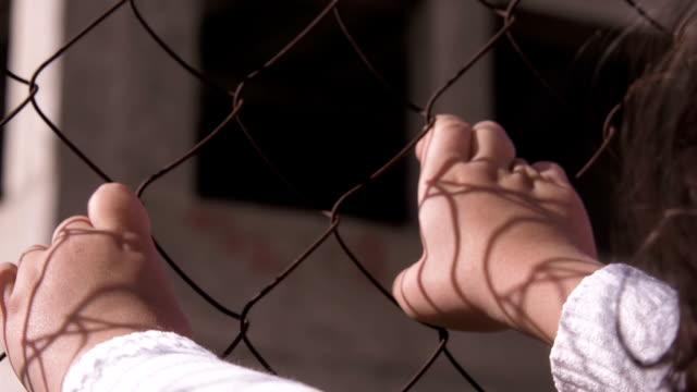obdachlose kinder. hände eines kindes auf einem metallgitter - käfig stock-videos und b-roll-filmmaterial