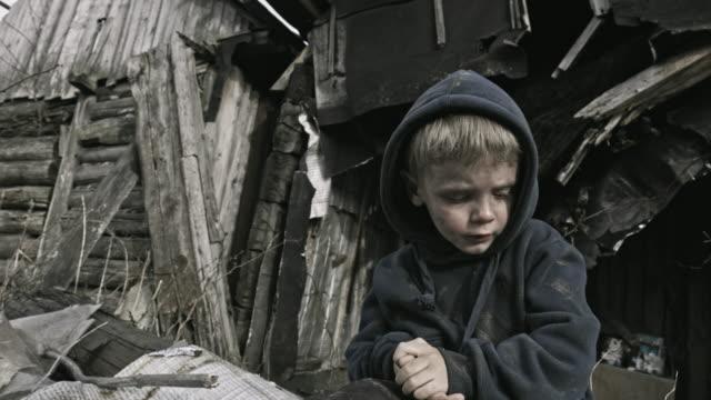 a homeless child on the ruins. refugee. - głodny filmów i materiałów b-roll